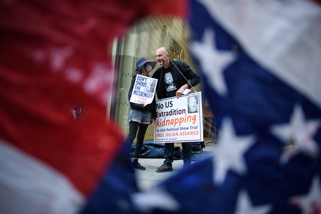 Supporters of the Wikileaks founder Julian Assange are seen through a torn US flag as they gather outside the Old Bailey on September 14, 2020 in London, England. Mr. Assange is fighting an extradition request by the United States on charges of hacking and espionage, avoided for years by seeking refuge in London's Ecuadorian embassy in 2012. (Photo by Leon Neal/Getty Images)