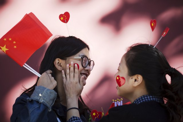 Girls offer flags, stickers and hairpins in national colours to people gathering near Tiananmen Gate to celebrate National Day marking the 66th anniversary of the founding of the People's Republic of China in Beijing October 1, 2015. (Photo by Damir Sagolj/Reuters)