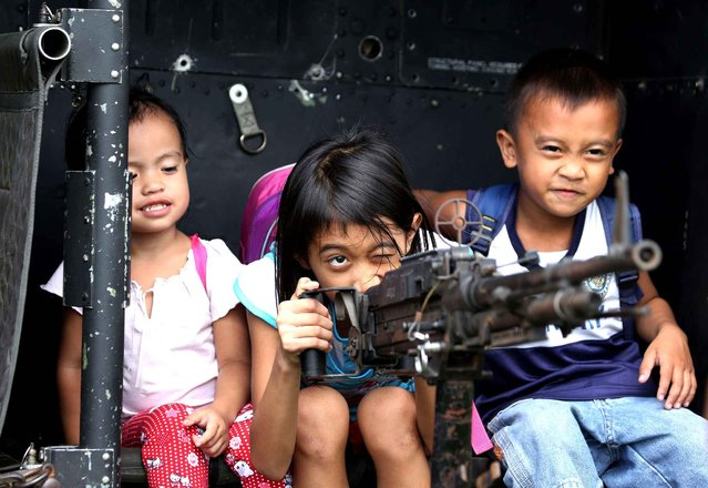 Filipino children play with a machine gun mounted on a Philippine UH-1H military helicopter during a static display to celebrate the 75th year anniversary of the Department of National Defense at Camp Aguinaldo military headquarters in suburban Quezon City, Philippines on Sunday, November 16, 2014. (Photo by Aaron Favila/AP Photo)