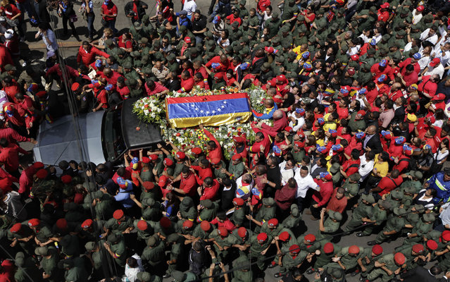 Military escort the passage of the procession through the streets of Caracas. (Photo by Ariana Cubillos/AP Photo)