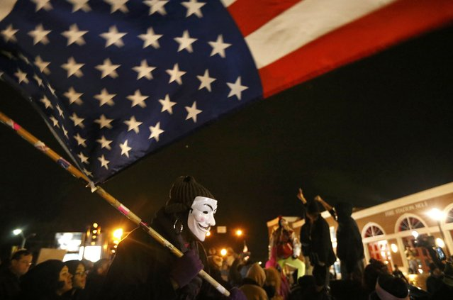A protester wearing a Guy Fawkes mask carries an American flag outside the Ferguson Police Department in Ferguson, Missouri, November 24, 2014. (Photo by Jim Young/Reuters)