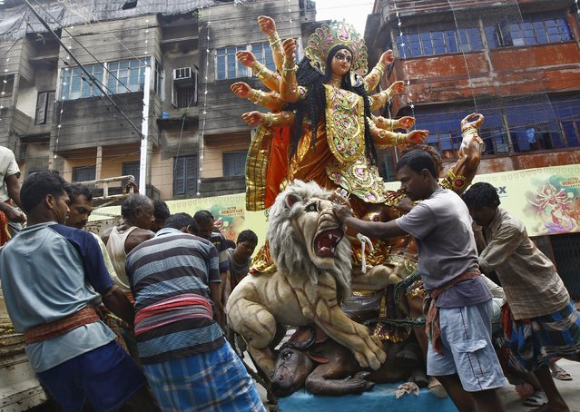 Workers load an idol of Hindu goddess Durga on a truck, which is to be transported on a pandal or a temporary platform ahead of the Durga Puja festival in Kolkata, India, October 15, 2015. The Durga Puja festival will be celebrated from October 19 to 22, which is the biggest religious event for Bengali Hindus. Hindus believe that the goddess Durga symbolizes power and the triumph of good over evil. (Photo by Rupak De Chowdhuri/Reuters)