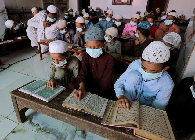 Children wearing face masks to prevent the spread of coronavirus read the Quran at a . religious school in a mosque, in Karachi, Pakistan, Saturday, September 19, 2020. (Photo by Fareed Khan/AP Photo)
