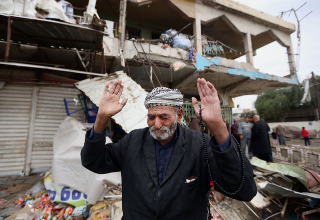 An Iraqi man reacts at the site of Monday's car bomb explosion, in the Shaab neighborhood of Baghdad, Iraq, Tuesday, November 25, 2014. Iraqi officials say a car bomb near a crowded marketplace in Baghdad has killed and wounded civilians. (Photo by Hadi Mizban/AP Photo)
