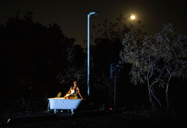 """The moon rises above as a dancer from Heidi Duckler Dance wearing a facemask performs during an event as part of the company's 35th anniversary celebration entitled """"The Quest"""" at the Baldwin Hills Scenic Overlook, October 2, 2020, in Culver City, California. The company is holding drive-up shows amid the coronavirus pandemic. (Photo by Valerie Macon/AFP Photo)"""