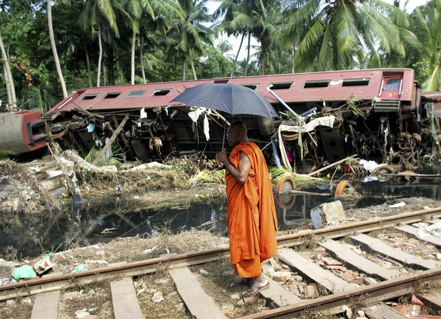 A Buddhist monk looks at a wrecked carriage after an entire train was destroyed by Sunday's tsunami in the town of Paraliya, south of Colombo in this December 30, 2004 file photo. (Photo by Kieran Doherty/Reuters)