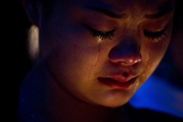 A fan of the late Hong Kong canto-pop star Leslie Cheung cries during a candlelight vigil in Hong Kong April 1, 2013. Exhibitions, concerts and tribute events are held in Hong Kong to mark the 10th anniversary of the death of Cheung, who leapt to his death from a hotel on April 1, 2003. (Photo by Tyrone Siu/Reuters)