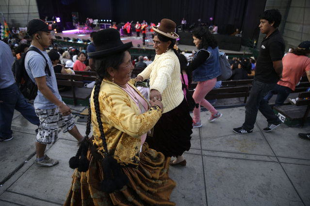 "Two Andean Indian women, dance during the inauguration of the ""People's Summit"" in Lima, Peru, Monday, December 8, 2014. The ""People's Summit"" is an alternative forum that demands that climatic justice should be reflected in international and national policies, and will be held parallel to the Climate Change Conference ""COP20"". (Photo by Martin Mejia/AP Photo)"