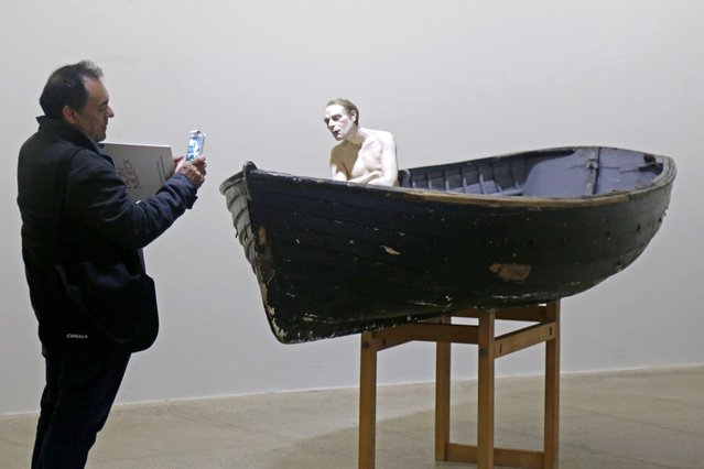 "A visitor takes a picture of a sculpture entitled ""Man in a Boat"" (2002) by artist Ron Mueck during the press day for his exhibition at the Fondation Cartier pour l'art contemporain in Paris April 15, 2013. (Photo by Charles Platiau/Reuters)"