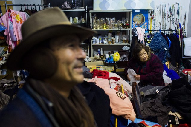 Regular customer Yoshiyuki Matsuura (L) visits a friend's indoor second hand clothes store at Boroichi flea market in Tokyo December 16, 2014. About 200,000 people flock to the market, which is only open for four mid-winter days a year - two in December and two in January - to buy, browse, or just soak up the atmosphere. (Photo by Thomas Peter/Reuters)