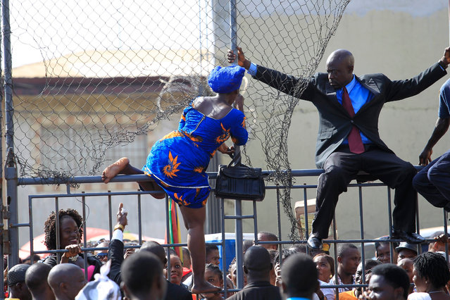 Liberians jump over a fence to seek divine healing during a church service in Monrovia, Liberia, 11 October 2016. The service, organized by Omega Fire Ministries and led by Apostle Johnson Suleman of Nigeria, will take place from 10 to 11 October at the Antoinette Tubman Stadium in Monrovia. Liberia is predominantly a Christian nation and thousands of Christians, including the people with disabilities, the elderly, and others experiencing social and spiritual complexities converged at the stadium to seek divine solutions to their ailments and problems. (Photo by Ahmed Jallanzo/EPA)