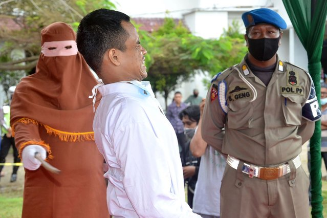 A man is publicly flogged by a member of the Sharia police after he was found guilty of raping a child, in Idi Rayeuk, East Aceh on November 26, 2020. (Photo by Cekmad/AFP Photo)