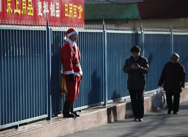 A security guard wearing a Santa Claus costume stands in front of the wall of the shopping mall in Beijing December 24, 2014. The shopping mall in Beijing deployed Santa Claus costumed guards in the mall to attract customers during the Christmas shopping season. (Photo by Kim Kyung-Hoon/Reuters)