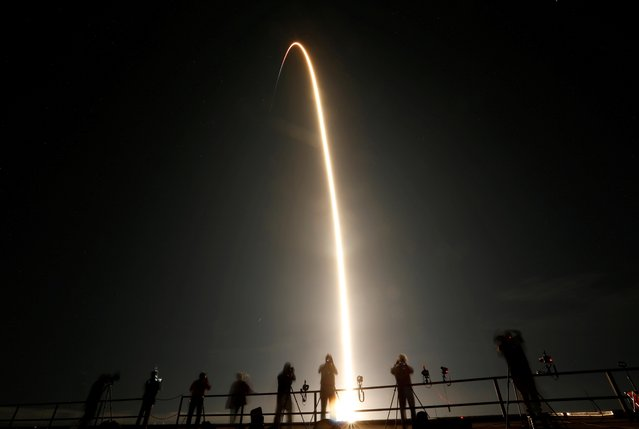 People watch as a SpaceX Falcon 9 rocket, topped with the Crew Dragon capsule, is launched carrying four astronauts on the first operational NASA commercial crew mission at Kennedy Space Center in Cape Canaveral, Florida, November 15, 2020. Elon Musk's rocket company SpaceX launched four astronauts on a flight to the International Space Station, NASA's first full-fledged mission sending a crew into orbit aboard a privately owned spacecraft. (Photo by Joe Skipper/Reuters)