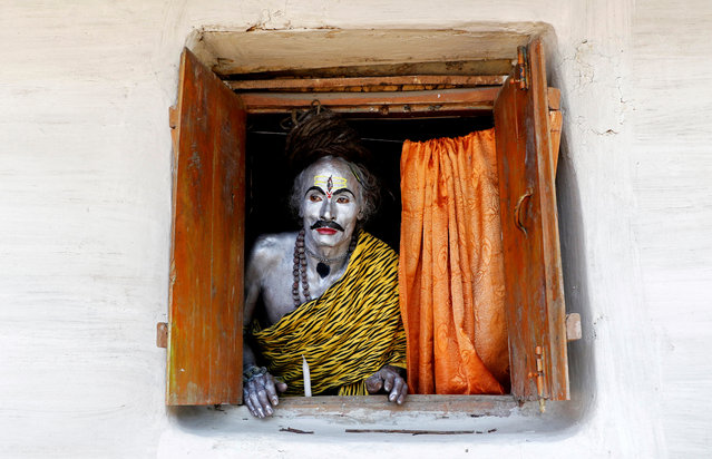 A devotee, dressed as Hindu God Shiva, looks out from a window as he waits to perform during the annual Shiva Gajan religious festival on the outskirts of Agartala, India April 13, 2018. (Photo by Jayanta Dey/Reuters)