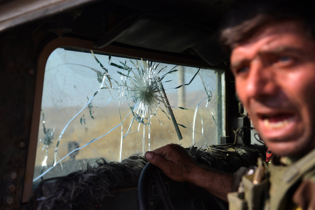 A Kurdish Peshmerga fighter leans out of his military vehicle which has taken several direct hits from ISIS snipers including on the windscreen on October 18, 2016 in the small town of Bartella near Mosul, Iraq. Joint forces from countries including Britain, U.S.A and France have joined Iraq and Iraqi Kurdistan to launch what is believed to be the largest ground operation since the invasion of Iraq in 2003 to retake Iraq's second largest city from the Islamic State who have held it since 2014. (Photo by Carl Court/Getty Images)