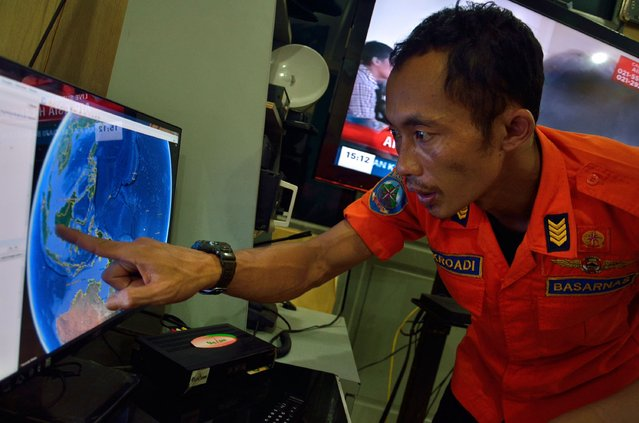 An official from Indonesia's national search and rescue agency in Medan, North Sumatra points at his computer screen to the position where AirAsia flight QZ8501 went missing off the waters of Indonesia on December 28, 2014. (Photo by Sutanta Aditya/AFP Photo)