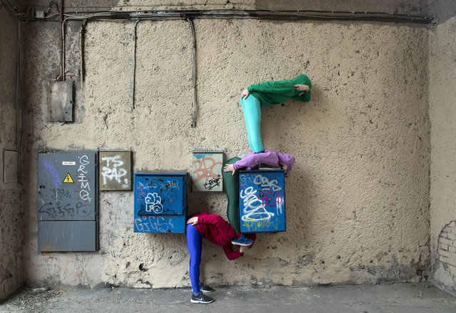 Performers present the Bodies in Urban Spaces project from Austrian artist Willi Dorner, in Vilnius, Lithuania, Saturday, April 28, 2018. (Photo by Mindaugas Kulbis/AP Photo)