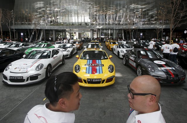 Members of the local Porsche motoring club chat during an event in Singapore's central business district July 24, 2015. (Photo by Edgar Su/Reuters)