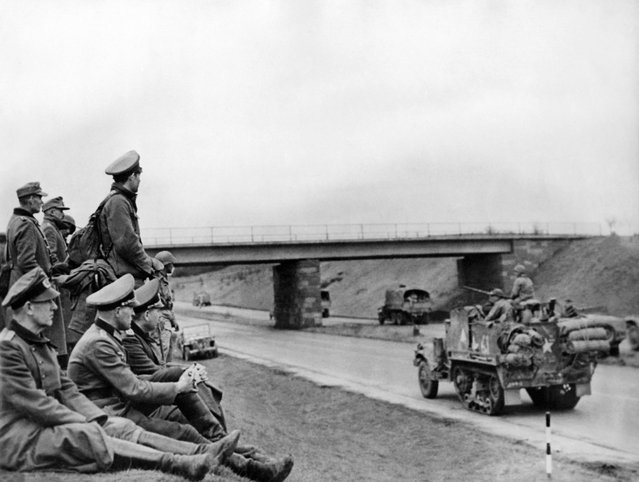 Picture released on April 18, 1945 of German officers sitting on the side of the road watching tanks of the Allies using the autostrades, motorways built by Hitler for his troops. (Photo by AFP Photo)