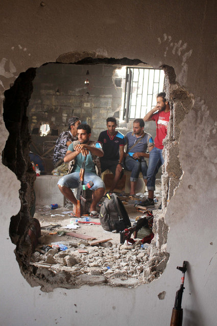 Fighters of Libyan forces allied with the U.N.-backed government are pictured through a hole in a house as they gather near the front line of fighting with Islamic State militants in Ghiza Bahriya district, in Sirte, Libya, October 28, 2016. (Photo by Hani Amara/Reuters)