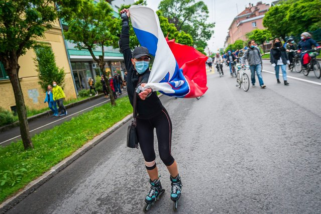 A Slovenian citizen, wearing a protective mask, waves a Slovenian flag, on May 15, 2020, as she takes part in a demonstration to block the centre of the capital Ljubljana, to protest against the centre-right government, accusing it of corruption and of using the COVID-19 (the novel coronavirus) crisis to restrict freedom. (Photo by Jure Makovec/AFP Photo)