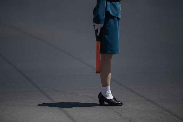 In a photo taken on June 5, 2017 a traffic security officer stands on duty at an intersection in Pyongyang. Officially known as traffic security officers but universally referred to as traffic ladies, they are chosen for their looks in a society that remains traditionalist in many respects. They must leave the role if they marry, and have a finite shelf-life, with compulsory retirement looming at just 26. The 300-odd ladies are unique to Pyongyang, which North Korean authorities are always keen to present in the best possible light despite their nuclear-armed country's impoverished status, and ensure a steady supply of photogenic young women who are the favourite subject of visiting tourists and journalists. (Photo by Ed Jones/AFP Photo)