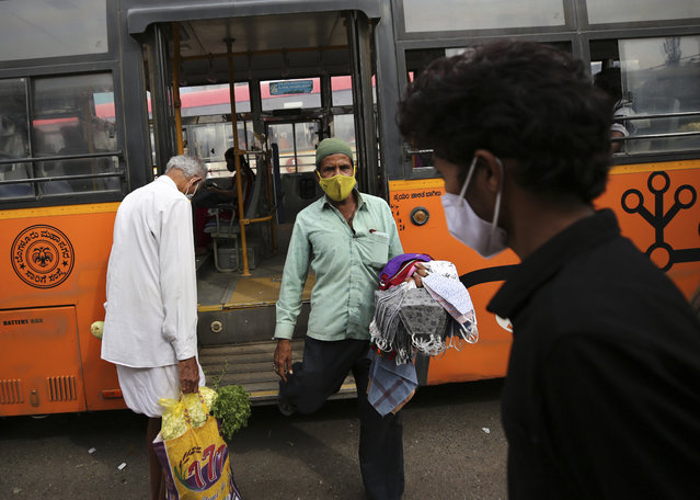 A vendor selling face masks disembarks a bus as he looks for prospective buyers at a bus station in Bengaluru, India, Tuesday, January 5, 2021. (Photo by Aijaz Rahi/AP Photo)