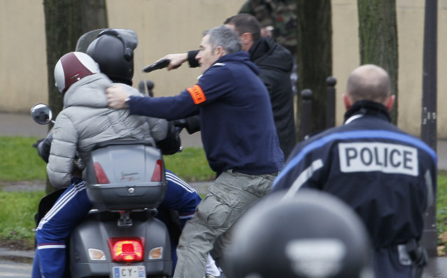 French police forcibly stop at gun point young people on a scooter as they arrive near the scene of a hostage taking at a kosher supermarket near Porte de Vincennes in eastern Paris January 9, 2015. Several people were taken hostage at a kosher supermarket in eastern Paris on Friday after a shootout involving a man armed with two guns, a police source said. (Photo by Youssef Boudlal/Reuters)