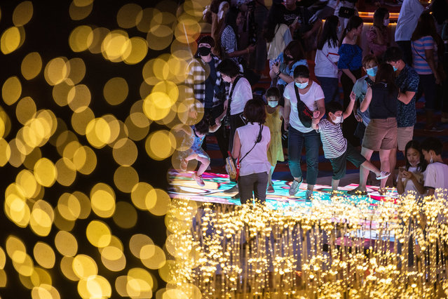 People visit light show to celebrate Christmas and New Year at Central World Department Store in downtown during New Year's Eve on December 31, 2020 in Bangkok, Thailand. Thailand welcomed the new year under a cloud of uncertainty, as sporadic outbreaks of the Covid-19 virus in clusters around the country worried both the public and health experts. (Photo by Sirachai Arunrugstichai/Getty Images)
