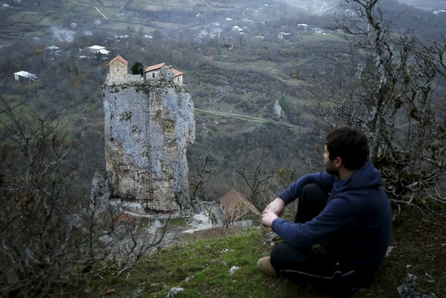 A local man looks at a church on top of the Katskhi Pillar, rock mass about 40 meters high, in the village of Katskhi, Georgia, November 27, 2015. The church, built in the ninth century, was later abandoned and it collapsed but was rebuilt in 2003, according to local media. (Photo by David Mdzinarishvili/Reuters)