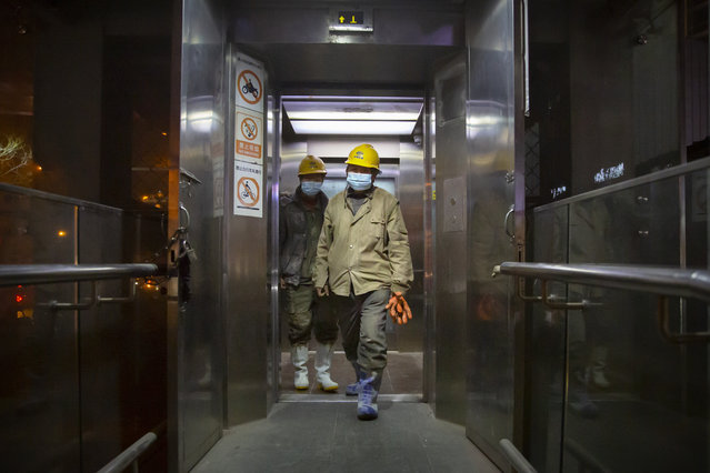 Construction workers wearing face masks to protect against the spread of the coronavirus exit an elevator in Beijing, Wednesday, January 13, 2021. China is concentrating its pandemic prevention efforts in the rural areas as officials urge people to not travel home for the annual Lunar New Year festival, as the country combats its most serious latest outbreak of COVID-19 since the pandemic originally broke out in Wuhan a year ago. (Photo by Mark Schiefelbein/AP Photo)