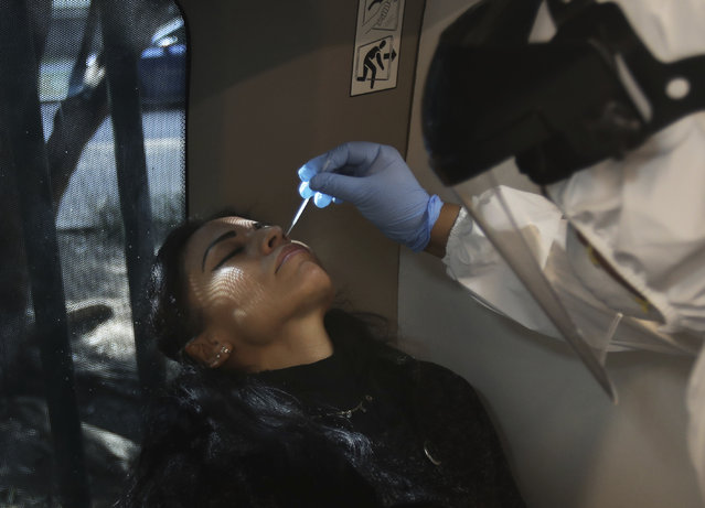 Dr. Alejandra Saavedra takes a nasal swab sample to test for COVID-19 at the Angela Peralta Theater in Mexico City, Saturday, January 23, 2021. As in many nations, the new coronavirus pandemic's pace has been uneven across Mexico. Mexico City remains the country's epicenter, with 89% of its hospital beds full. (Photo by Marco Ugarte/AP Photo)