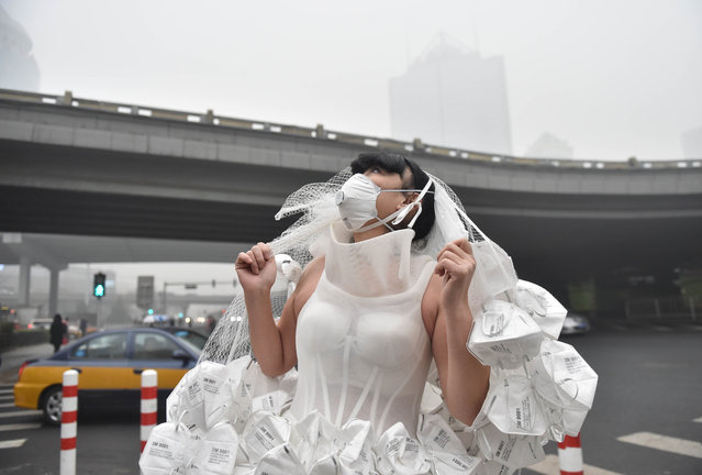 Artist Kong Ning wears a wedding dress made from respirators to highlight concerns about air quality and pollution in Beijing, China on December 1, 2015. (Photo by Luo Xiaoguang/Xinhua Press/Corbis)