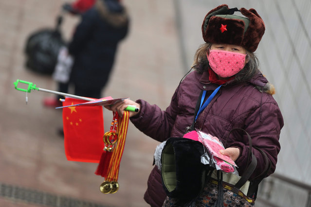 A vendor wears mask to sell national flag and selfie stick at Tiananmen Square during a haze day in Beijing city, China, 08 December 2015. Beijing has issued its first red alert for air pollution under a four-tier emergency response system created in October 2013. The red alert which is the most serious level for Air Quality Index (AQI), last from 7 a.m. on 08 December to 12 a.m. on 10 December. (Photo by Wu Hong/EPA)