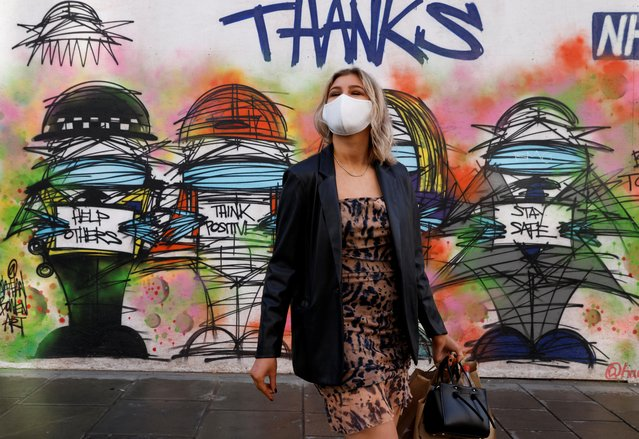 A woman wearing a face mask stands in front of graffiti, amid the coronavirus disease (COVID-19) outbreak, in central London Britain on October 15, 2020. (Photo by John Sibley/Reuters)