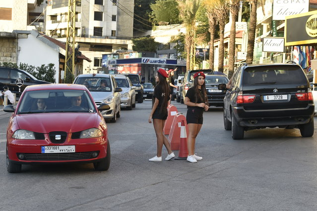 Lebanese university students wearing municipality police costume regulate the traffic in the village of Brummana, east Beirut, Lebanon, 23 June 2018. (Photo by Wael Hamzeh/EPA/EFE)