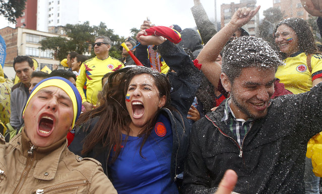 In this Thursday, June 28, 2018 photo, fans of Colombia's national soccer team celebrate their team's victory over Senegal after watching a live telecast of the match between Senegal and Colombia, at the 2018 soccer World Cup, in Bogota, Colombia. (Photo by Daniel Munoz/AP Photo)