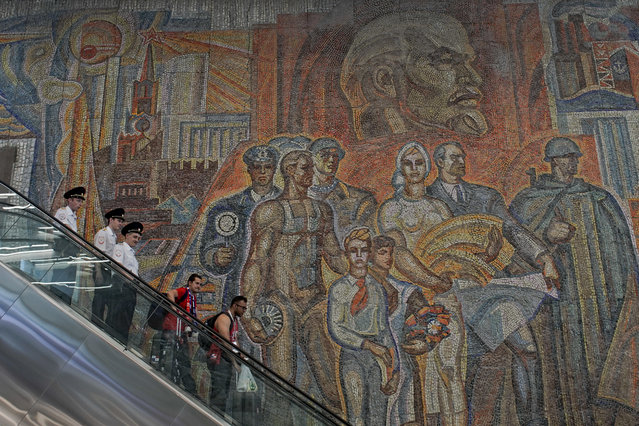 In this Monday, June 25, 2018 filer, soccer fans and police ride down an escalator at a subway station in front of a large soviet-era mural depicting Soviet founder Vladimir Lenin, top, in Nizhny Novgorod, Russia. (Photo by Victor R. Caivano/AP Photo)