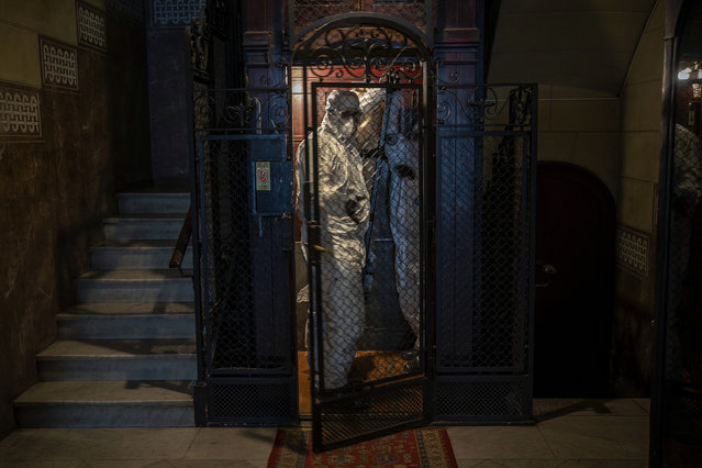 Wearing protective suits to prevent infection, mortuary workers move the body of an elderly person who died of COVID-19 from an elevator after removing it from a nursing home in Barcelona, Spain, Friday, November 13, 2020. (Photo by Emilio Morenatti/AP Photo)