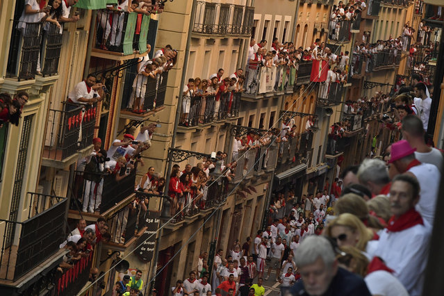 People on balconies wait for the start on the third day of the running of the bulls at the San Fermin Festival in Pamplona, northern Spain, Monday, July 9, 2018. Revellers from around the world flock to Pamplona every year to take part in the eight days of the running of the bulls. (Photo by Alvaro Barrientos/AP Photo)