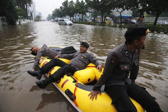 Policemen rest on an inflatable raft at the flooded Kelapa Gading business district in Jakarta, January 23, 2015. (Photo by Reuters/Beawiharta)