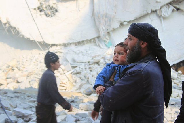 A rescue worker holds an injured boy after what activists said were airstrikes carried out by the Russian air force in Idlib city, Syria December 20, 2015. (Photo by Ammar Abdullah/Reuters)
