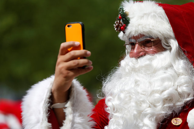 A man dressed as Santa Claus records on his cellphone as he takes part in the World Santa Claus Congress, an annual event held every summer in Copenhagen, Denmark, July 23, 2018. (Photo by Andrew Kelly/Reuters)