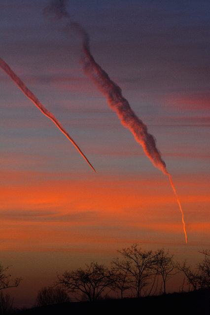The contrails of two airplanes fade in the sky as the rising sun adds a spectatcular color cast to the landscape in Hajdusamson, 232 kilometers east of Budapest, on 13 January 2015 morning. (Photo by Zsolt Czegledi/EPA)