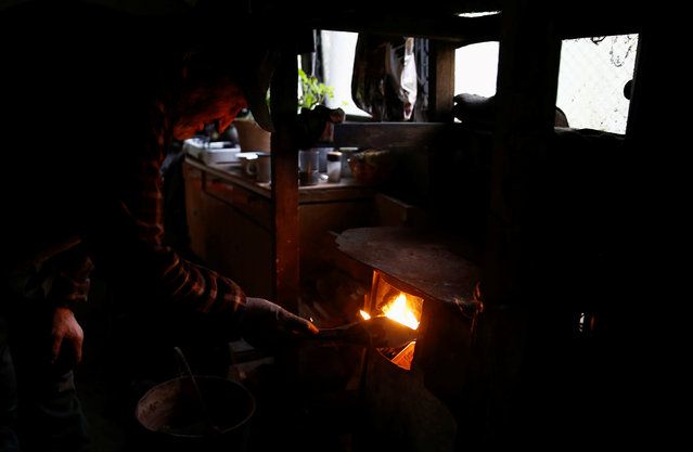 Charcoal burner Zygmunt Furdygiel fires wood stove inside his hut at a charcoal making site in the forest of Bieszczady Mountains, near Baligrod village, Poland October 27, 2016. (Photo by Kacper Pempel/Reuters)
