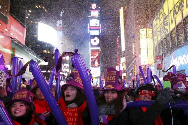Revelers gather as confetti falls during New Year celebrations in Times Square in the Manhattan borough of New York. December 31, 2015. (Photo by Andrew Kelly/Reuters)