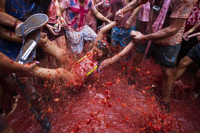 """Revellers take part in the annual """"Tomatina"""" festivities in Bunol, near Valencia, on August 28, 2013. Twenty thousands revellers hurled 130 tonnes of squashed tomatoes at each other, drenching the streets in red in a gigantic Spanish food fight known as the Tomatina. (Photo by Gabriel Gallo/AFP Photo)"""