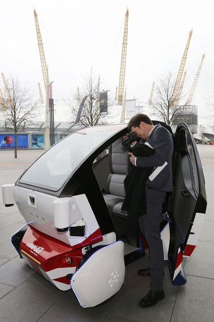 A member of the media photographs a prototype of a Lutz Pathfinder driverless vehicle is displayed to members of the media in Greenwich, east London, February 11, 2015. (Photo by Suzanne Plunkett/Reuters)