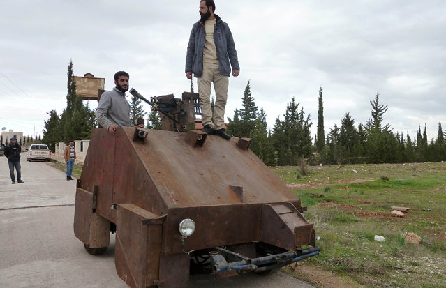 """Syrian rebels stand atop Sham II, a homemade armoured vehicle made by the rebels' Al-Ansar brigade, in Bishqatin, 4 kms west of Aleppo, on December 8, 2012. The Sham II, which was cobbled together from the chassis of an old diesel car and parts salvaged from a junkyard in under a month, uses a controller from a Sony Playstation games console to aim a roof-mounted machine gun. Inside the rusting steel panels a crew of two sit side-by-side in front of flatscreen TV's mounted on the wall. Sham II, named after ancient Syria, touted by rebels as """"100 percent made in Syria"""". (Photo by Herve Bar/AFP Photo)"""
